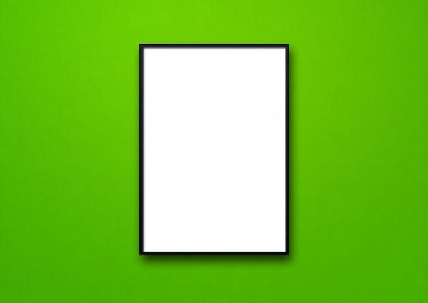 Czarna ramka na zdjęcia wisząca na zielonej ścianie