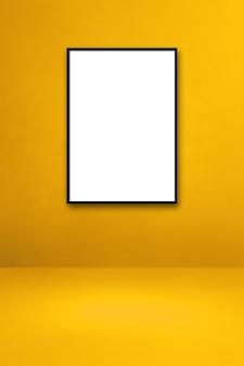 Czarna ramka na zdjęcia wisząca na żółtej ścianie. pusty szablon makiety