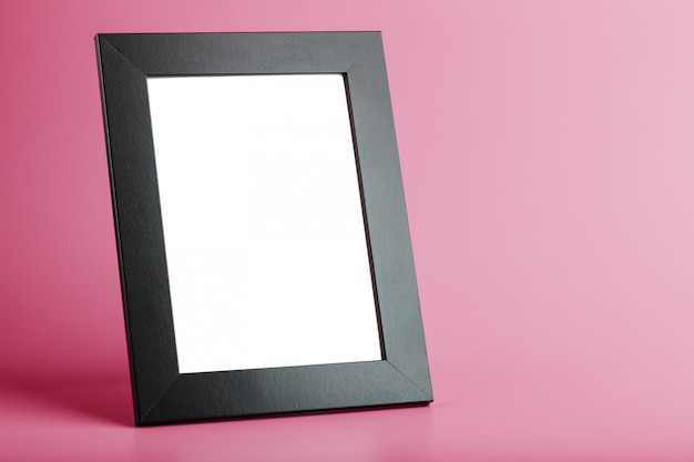 Czarna ramka na zdjęcia z pustą przestrzenią na różowym tle.
