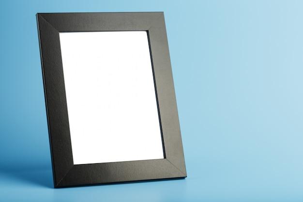 Czarna ramka na zdjęcia z pustej przestrzeni na niebieskim tle.