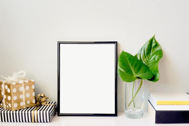 Czarna ramka na zdjęcia, zielona roślina w kryształowym wazonie, pudełka na prezenty i stos książek ułożonych na pustej szarej ścianie.