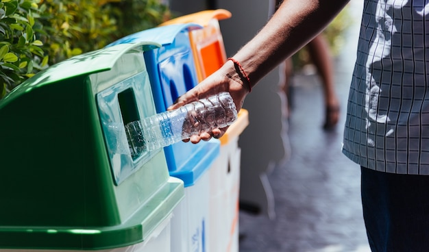 Czarna ręka mężczyzny rzucająca pustą plastikową butelkę po wodzie do recyklingu śmieci