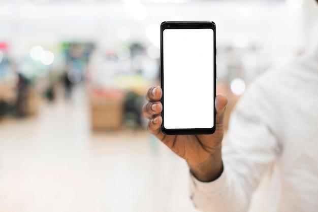 Czarna ręka pokazuje telefon komórkowego na zamazanym tle