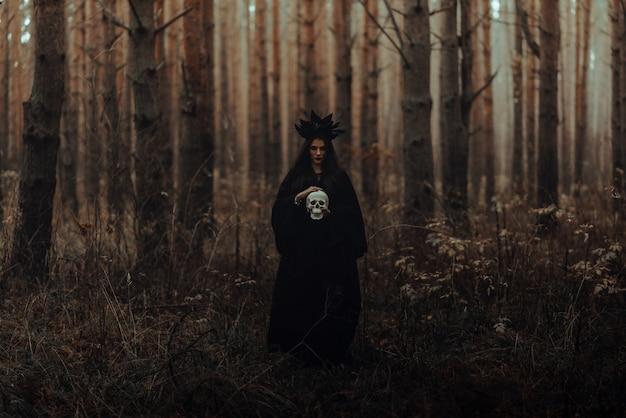 Czarna straszna wiedźma trzyma w rękach czaszkę martwego mężczyzny w ciemnym lesie