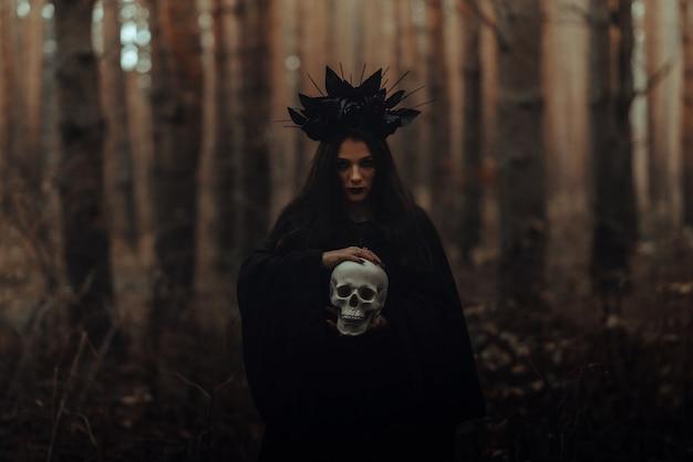 Czarna straszna wiedźma z czaszką w rękach martwego mężczyzny w lesie