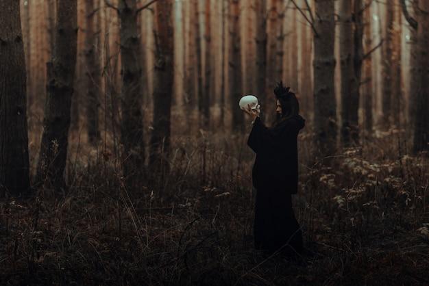 Czarna straszna wiedźma z czaszką w rękach zmarłego wykonuje w lesie okultystyczny mistyczny rytuał