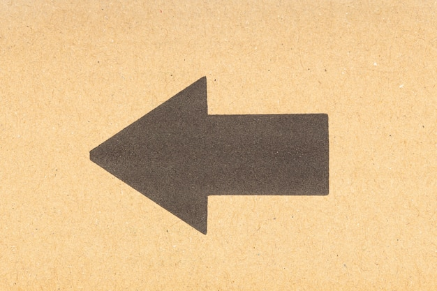 Czarna strzałka skierowana w lewo na brązowym tle kartonu. ścieśniać