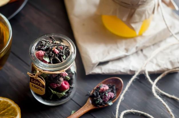 Czarna sucha herbata z liśćmi mięty i suchą maliną w słoiku i drewnianą łyżką na ciemnym drewnianym stole, przekąska owocowa, miód i pastylka przytulny czas na herbatę. naturalne światło, selektywne ogniskowanie