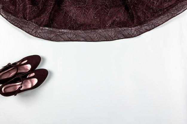 Czarna sukienka koktajlowa, buty na jasnym tle.
