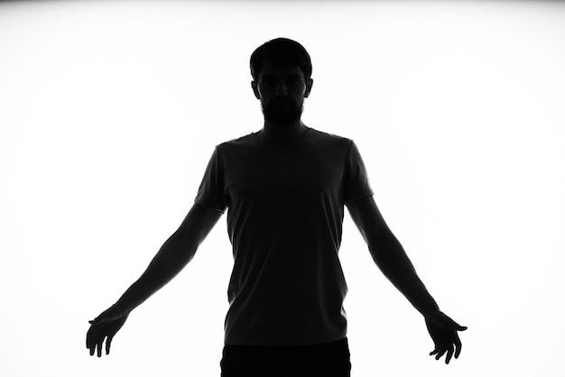 Czarna sylwetka mężczyzny, który gestykuluje rękami na jasnym tle.