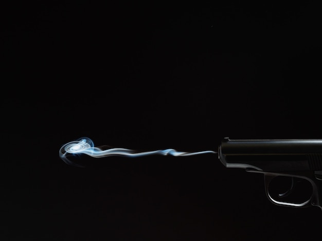 Czarna sylwetka pistoletu z dymem