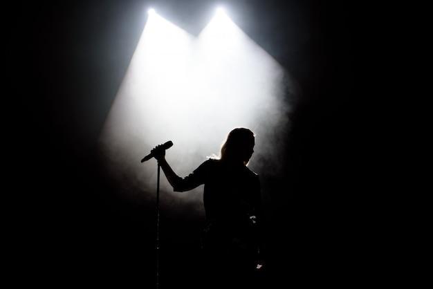 Czarna sylwetka wokalistki z białymi reflektorami