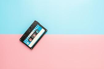 Czarna taśma kaseta na błękitnym i różowym tle.