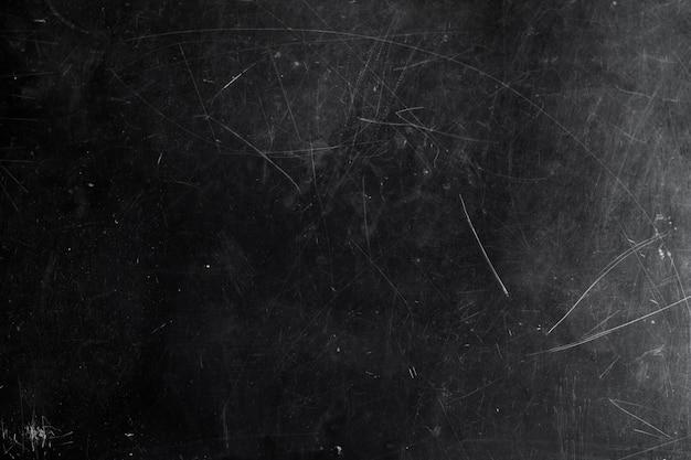 Czarna tablica kredowa z zadrapaniami i zadrapaniami