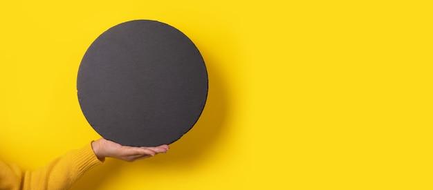 Czarna tablica łupkowa w ręku na żółtym tle, puste miejsce na menu lub przepis, panoramiczny obraz