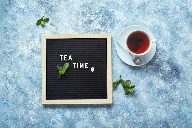 Czarna tablica na herbatę z tekstem na niebieskim stole ze szklaną filiżanką herbaty z liśćmi mięty