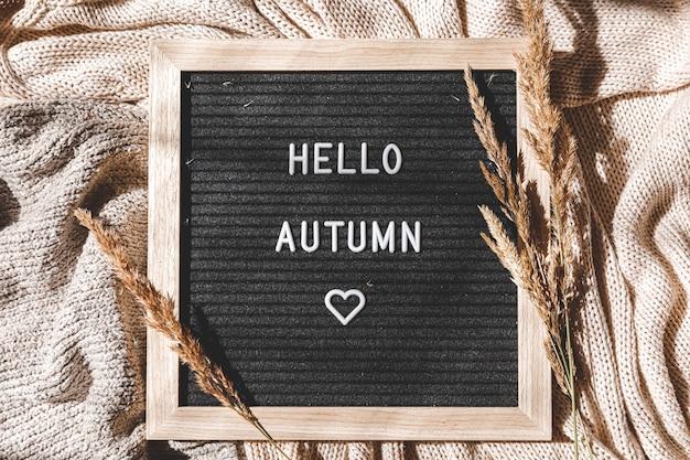 Czarna tablica z tekstem hello autumn i suszoną trawą leżącą na białym swetrze z dzianiny