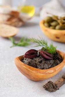 Czarna tapenade lub tapas, tradycyjne danie prowansalskie lub dip z oliwkami i bazylią na starym drewnianym stole tle. selektywne skupienie. widok z góry