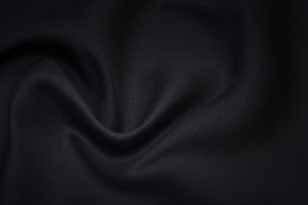 Czarna tkanina tekstura tło. pusta, luksusowa koszula waftowa z tkaniny i materiału.