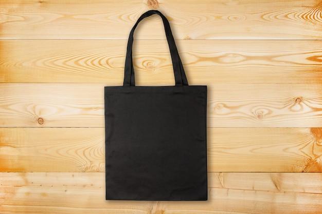 Czarna tkaniny torba na drewnianym tle