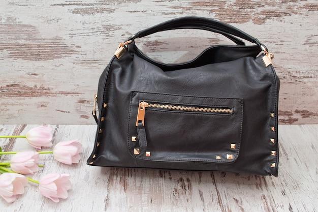 Czarna torba na drewnianym tle, różowi tulipany. modna koncepcja.
