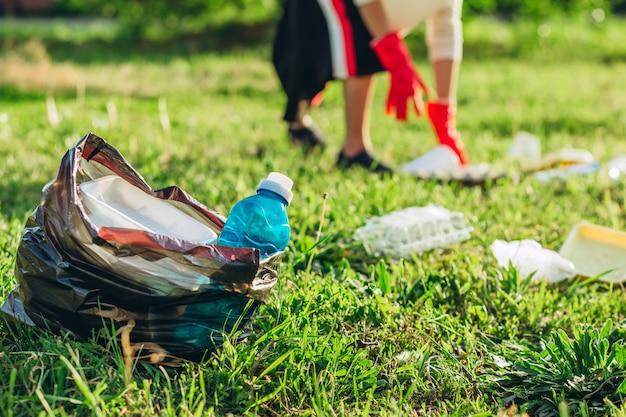 Czarna torba z koszem na pierwszym planie. damskie dłonie w czerwonych gumowych rękawiczkach. kobieta zbiera śmieci w torbie. wolontariusz zmiatania śmieci w lecie parku.