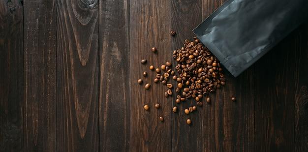 Czarna torebka foliowa do pakowania kawy i rozlane ziarna na drewnianym stole