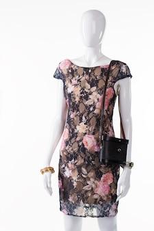 Czarna torebka vintage na manekinie. żeński manekin z torbą retro. sukienka w kwiaty i torebka vintage. ciemny, elegancki strój wieczorowy damski.