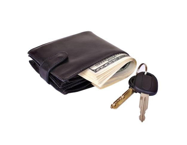 Czarna torebka wypchana papierowymi pieniędzmi i kluczykami do samochodu na białym tle