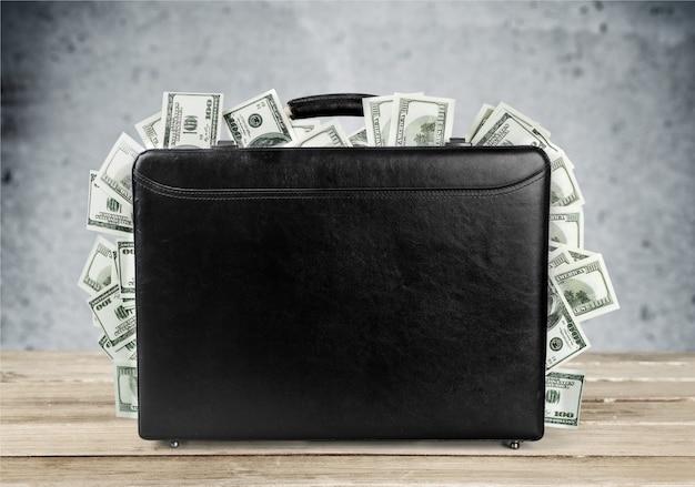 Czarna walizka pełna banknotów na tle
