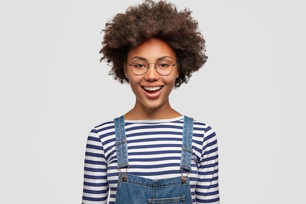 Czarna, wesoła, kręcona kobieta szczęśliwa z ukończenia udanego projektu, ubrana w swobodny sweter w paski i dżinsowy kombinezon