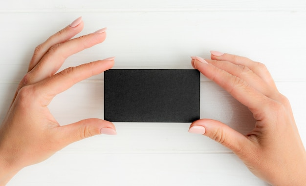 Czarna wizytówka w rękach dziewczyny