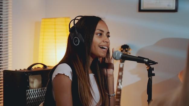 Czarna wokalistka w słuchawkach nagrywa swoją nową piosenkę w domowym studio