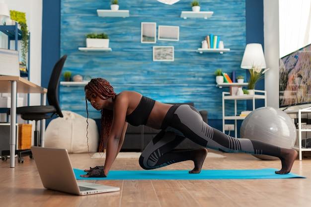 Czarna wysportowana kobieta trenująca na siłę mięśni, wykonująca pozycję wspinaczy górskich na macie do jogi, ubrana w sportowe legginsy, w domu w salonie postępując zgodnie z instrukcjami online