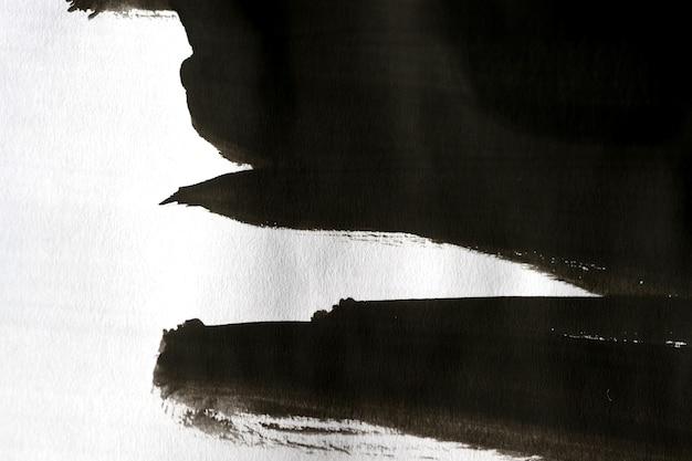 Czarne abstrakcyjne improwizowane pociągnięcia pędzlem na białym papierze z jedną ręką na białym tle