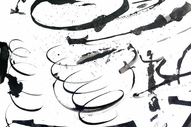 Czarne abstrakcyjne pociągnięcia pędzlem i plamy farby na papierze. grunge sztuki kaligrafii tło