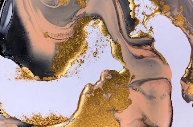 Czarne, beżowe i złote mieszane atramenty rozpryskiwane na tle białego papieru.