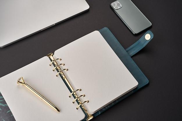 Czarne biurko z otwartym zielonym, ręcznie robionym notatnikiem ze złotym długopisem oraz szarym laptopem i smartfonem