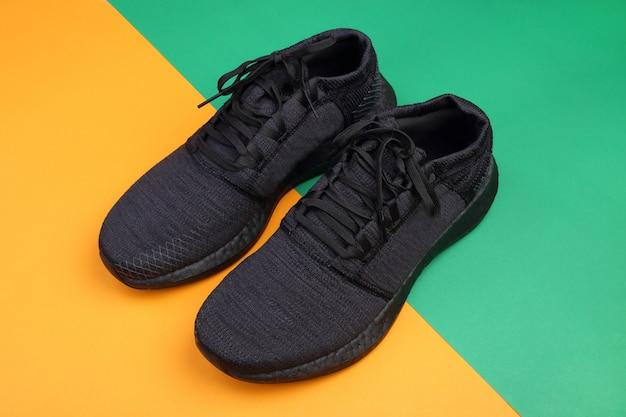 Czarne buty do biegania na zielonym i pomarańczowym pastelowym tle