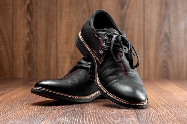 Czarne buty jedna czysta sekunda brudne na drewnianej ścianie. pojęcie połysku obuwia, pielęgnacji odzieży, usług.