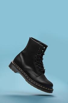 Czarne buty w powietrzu na niebieskim tle. modne buty martwa natura. klasyczne czarne sznurowane buty bojowe unisex. zamknij widok buta lewitacji z miejsca kopiowania tekstu