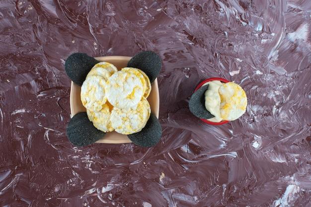 Czarne chipsy, chipsy serowe i jogurt w miskach, na marmurowym stole.