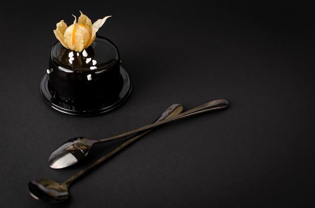 Czarne ciasto czekoladowe zwieńczone aksamitną polewą i ozdobione pęcherzycą na czarnym tle.