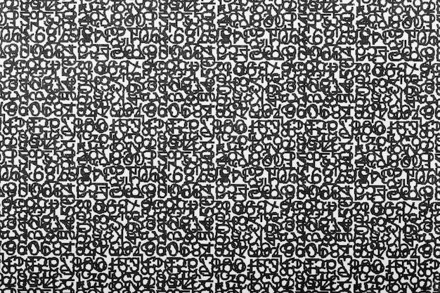 Czarne cyfry i litery na białej teksturze