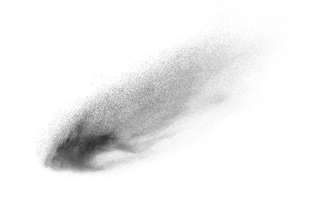 Czarne cząsteczki rozpryskują się na białym tle. wybuchający pył czarnego prochu.