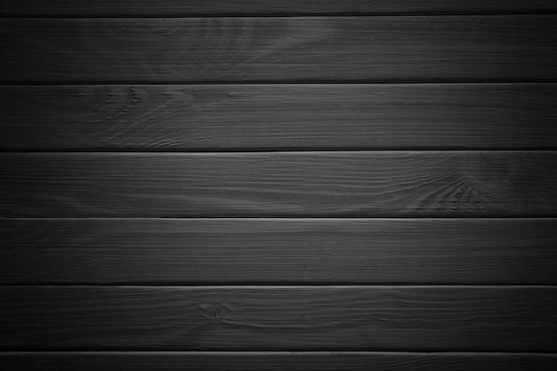 Czarne drewniane abstrakcyjne tło ze światłem i zadrapaniami, ciemne drewno tekstury