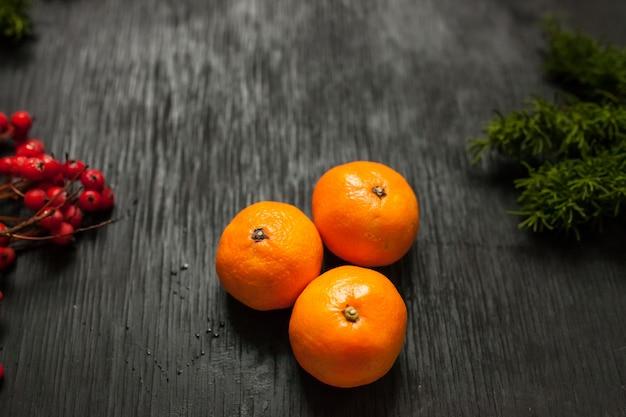 Czarne drewniane tła z mchu, popiołu i mandarynek po bokach. grunge tekstur