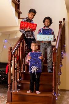 Czarne dzieci trzymają prezenty świąteczne chłopcy trzymają prezenty na schodach, wszyscy mówią, że ser...