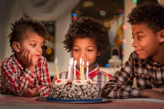 Czarne dzieci z tortem urodzinowym trzech chłopców przy stole urodzinowym z okazji urodzin brat oglądający c...