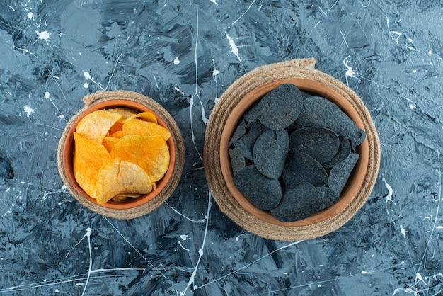 Czarne frytki i chipsy ziemniaczane w misce na podstawkach, na tle marmuru.